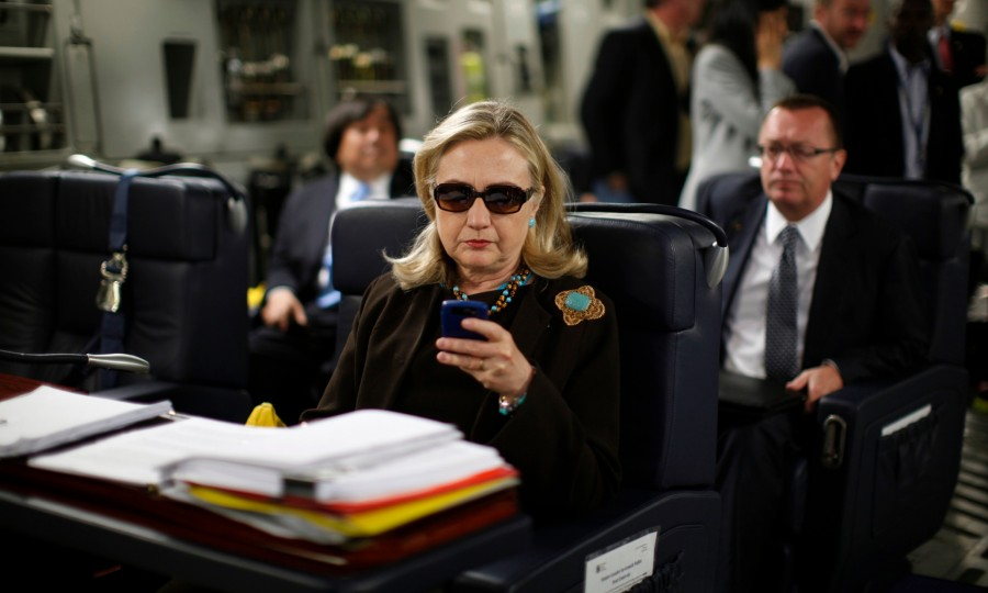 FILE - In this Oct. 18, 2011, file photo, then-Secretary of State Hillary Rodham Clinton works from a desk inside a C-17 military plane upon her departure from Malta, in the Mediterranean Sea, bound for Tripoli, Libya. Clinton has joined Twitter, describing herself as a pantsuit aficionado and a hair icon. The potential 2016 presidential candidates profile page shows the infamous photo of the stern-looking Clinton wearing dark sunglasses and reading her Blackberry. (AP Photo / Kevin Lamarque, Pool, File)