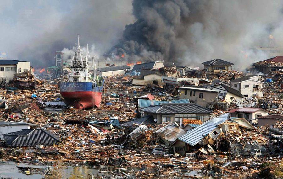 epa02628954 Amidst Tsunami flood waters burning houses and ships are piled in a mass of debris in  Kisenuma city, Miyagi prefecture, Japan, 12 March 2011.  A magnitude of 8.9 earthquake hit northern Japan on 11 March.  EPA/STR JAPAN OUT
