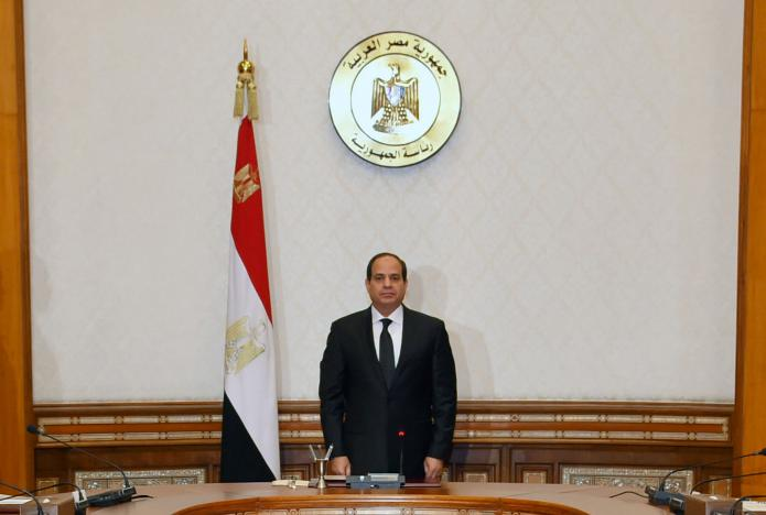 Egyptian President Abdel Fattah al-Sisi stands and holds a moment of silence for those killed