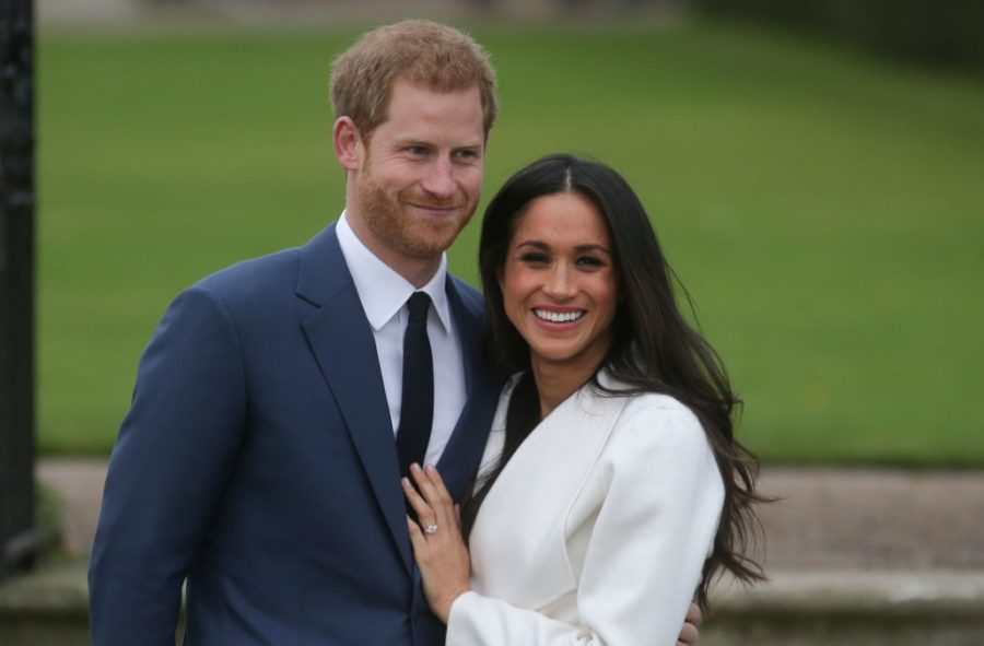 Britains Prince Harry stands with his fiancée US actress Meghan Markle as she shows off her engagement ring whilst they pose for a photograph in the Sunken Garden at Kensington Palace in west London on November 27, 2017, following the announcement of their engagement. Britains Prince Harry will marry his US actress girlfriend Meghan Markle early next year after the couple became engaged earlier this month, Clarence House announced on Monday. / AFP PHOTO / Daniel LEAL-OLIVAS        (Photo credit should read DANIEL LEAL-OLIVAS/AFP/Getty Images)