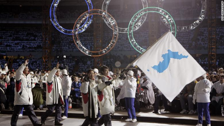 HOLD FOR USE WITH STORY SLUGGED SOUTH KOREA KOREAS TENSIONS SPORTS DIPLOMACY, FILE - In this Feb. 10, 2006, file photo, Korea flag-bearers Bora Lee and Jong-In Lee, carrying a unification flag lead their teams into the stadium during the 2006 Winter Olympics opening ceremony in Turin, Italy. (AP Photo/Amy Sancetta, File)