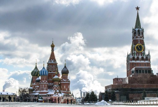 People walk in front of St. Basils Cathedral and the Kremlin on Red Square in Moscow on March 16, 2018. Russia will vote for President on March 18. / AFP PHOTO / Mladen ANTONOV