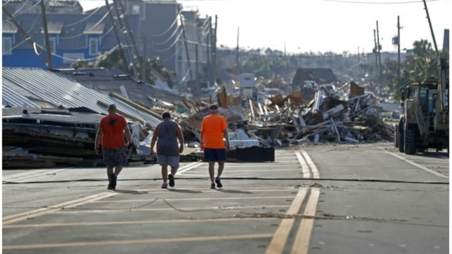 People walk amidst destruction on the main street of Mexico Beach, Fla., in the aftermath of Hurricane Michael inThursday, Oct. 11, 2018. (AP Photo/Gerald Herbert)