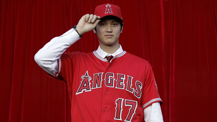 Baseball player Shohei Ohtani, of Japan, poses for photos after a news conference at Angel Stadium, Saturday, Dec. 9, 2017, in Anaheim, Calif. The Japanese star is bringing his arm and bat to the Los Angeles Angels, pairing him with two-time MVP Mike Trout. (AP Photo/Jae C. Hong)