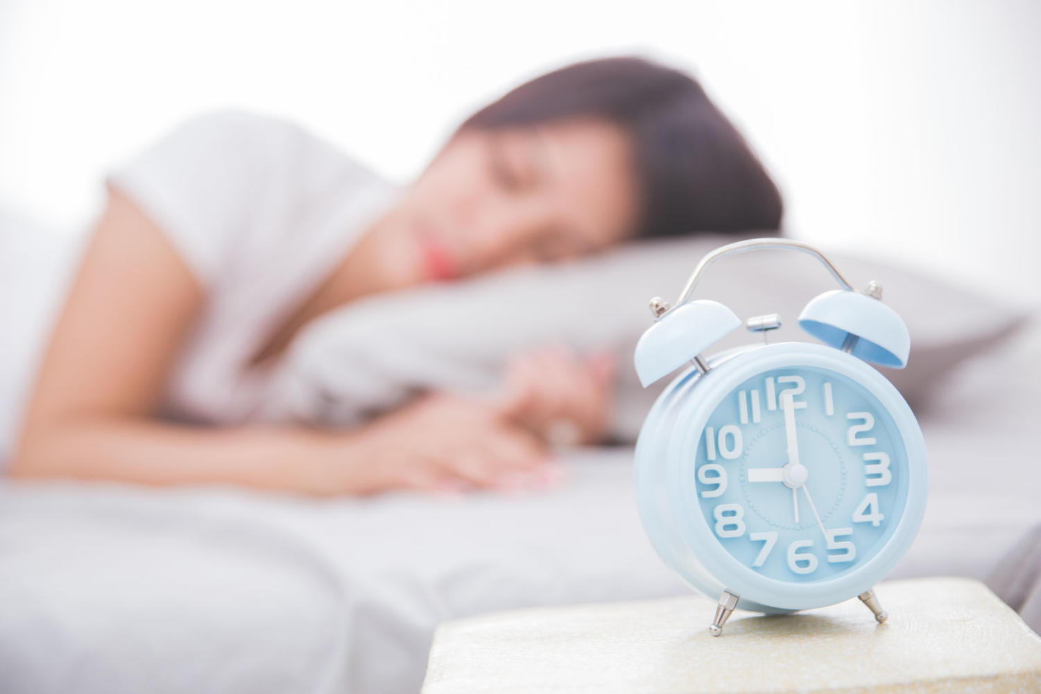 48377023 - alarm clock close up with woman sleeping peacefully on a bed on the back