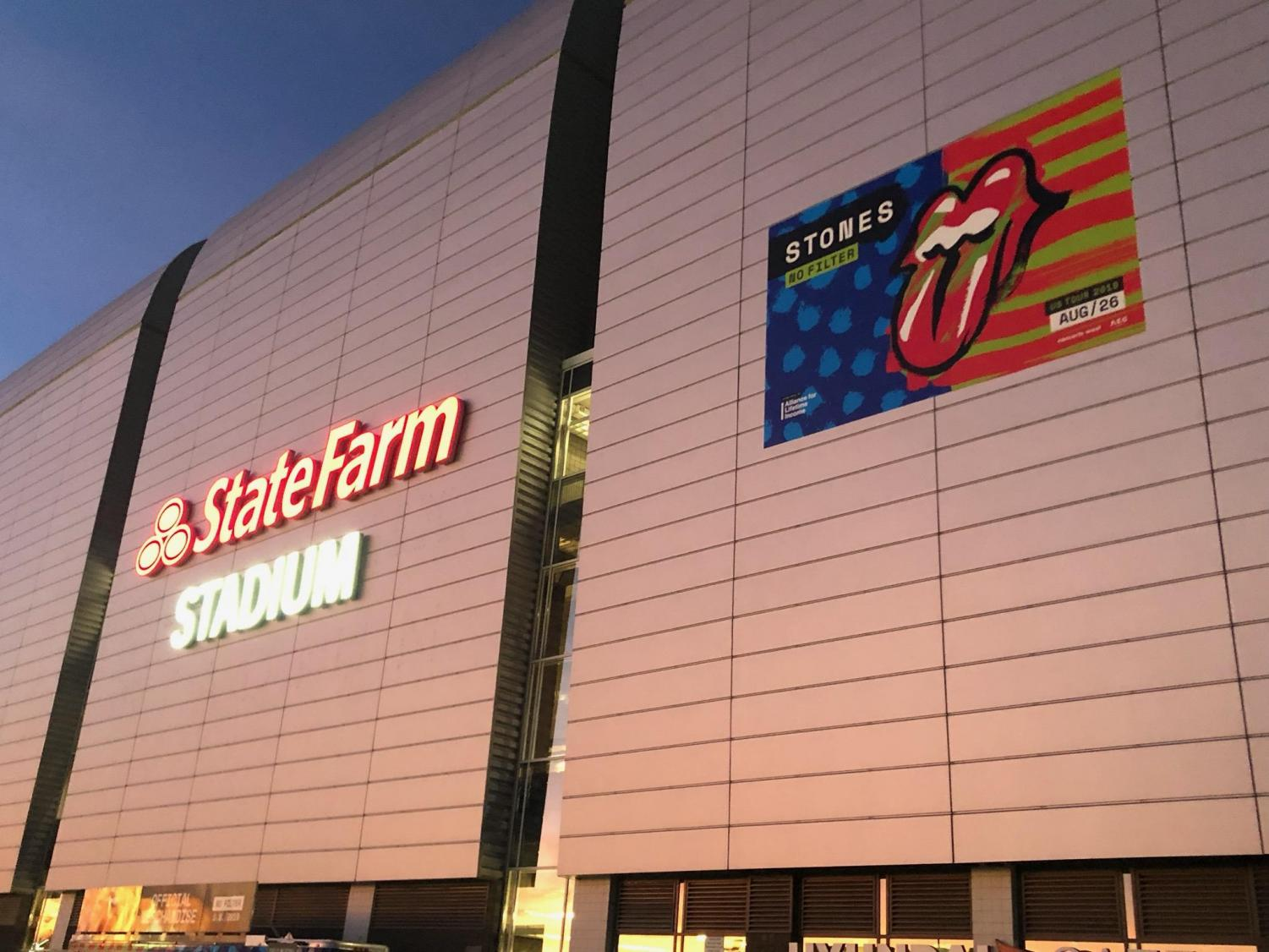 The outside of the State Farm Stadium with the poster for the show